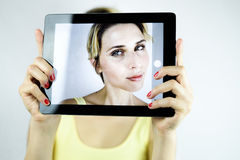 Pretty young woman taking a selfie with a white tablet. focus on Royalty Free Stock Photos