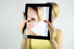 Pretty young woman taking a selfie with a white tablet. focus on Stock Photo