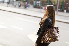 Pretty young woman talking on the mobile phone. On the city street Royalty Free Stock Photos