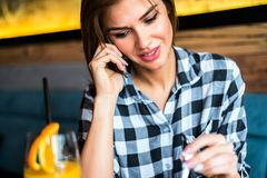 Pretty young woman talking on mobile phone. By table in the cafe Stock Image