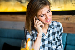 Pretty young woman talking on mobile phone. By table in the cafe Stock Photo