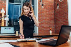Pretty young woman talking on phone counting using a calculator working at office standing at desk.  Royalty Free Stock Images