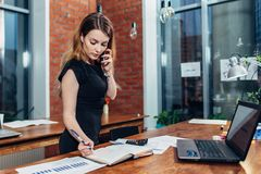 Pretty young woman talking on phone counting using a calculator working at office standing at desk stock images