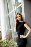 Pretty young woman talking on the phone in front of office Stock Photo