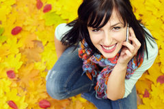 Pretty young woman talking on phone among leaves. Portrait of attractive young woman talking on the mobile phone and sitting on a carpet of yellow and red fallen Royalty Free Stock Photo