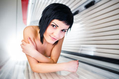 Pretty, young woman tanning her skin. In a modern sunbed Royalty Free Stock Image