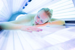 Pretty, young woman tanning her skin. In a modern sunbed Stock Photography