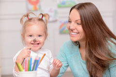 Pretty young woman is teaching her child to draw. Beautiful mother are her daughter are making fun at home. They have paint on their faces. The lady and girl are royalty free stock image