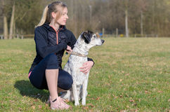 Pretty young woman teaching her dog commands. Kneeling down in a field alongside it looking to the side Stock Image