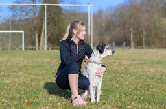 Pretty young woman teaching her dog commands. Kneeling down in a field alongside it looking to the side Royalty Free Stock Images
