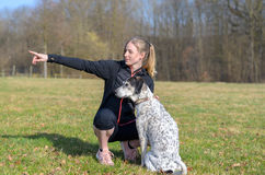 Pretty young woman teaching her dog commands. Kneeling down in a field alongside it pointing with her hand to the side Royalty Free Stock Image