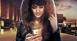 Pretty young woman texting somebody with her new samtphone. Cityscape Royalty Free Stock Photos