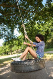 Pretty young woman in tire swing Royalty Free Stock Images