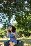Pretty young woman in tire swing Stock Photography