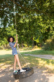 Pretty young woman in tire swing Royalty Free Stock Photos
