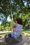 Pretty young woman in tire swing Royalty Free Stock Photography