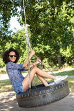 Pretty young woman in tire swing Stock Image