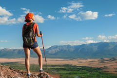 Pretty young woman tourist standing on top of mountain Stock Photo