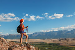 Pretty young woman tourist standing on top of mountain Stock Photos