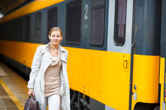 Pretty young woman at a train station Stock Photo