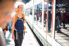 Pretty, young woman in a trainstation, waiting for her train. Boarding a train (color toned image Stock Images