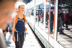 Pretty, young woman in a trainstation, waiting for her train. Boarding a train (color toned image Royalty Free Stock Photos