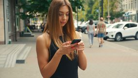 Pretty young woman typing on mobile phone with people walking in street at background, Brown haired woman looking at. Side view of pretty young woman typing on stock video