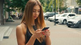 Pretty young woman typing on mobile phone with people walking in street at background, Brown haired woman looking at. Side view of pretty young woman typing on stock footage