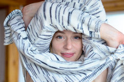 Pretty young woman undressing. Pulling a knitted cardigan or sweater over her head with her arms encircling her face Stock Photos