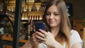 Pretty young woman uses a mobile phone in a cafe stock video footage