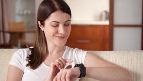 Woman at home texting on smart watch. Beautiful young female professional working on smartwatch. Pretty young woman using app on smartwatch at home smiling and stock video footage