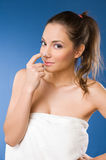 Pretty young woman using body milk. Stock Photos