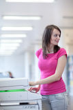 Pretty young woman using a copy machine Stock Image