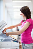 Pretty, young woman using a copy machine Stock Photography