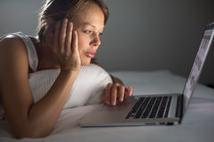 Pretty, young woman using her laptop computer in bed Stock Images