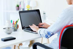Pretty young woman using her laptop in the office. Stock Images