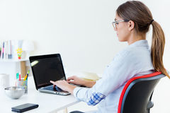 Pretty young woman using her laptop in the office. Royalty Free Stock Image