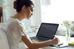 Pretty young woman using her laptop in the office. Royalty Free Stock Photography