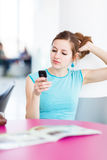 Pretty young woman using her mobile phone Stock Images