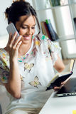 Pretty young woman using her mobile phone in the office. Stock Image