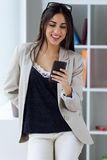 Pretty young woman using her mobile phone in the office. Stock Photo