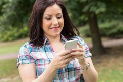 Pretty young woman using her mobile phone, outdoors Stock Images