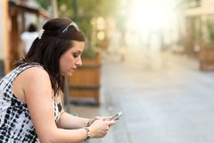 Pretty young woman using her mobile phone in the street, light effect Stock Photo