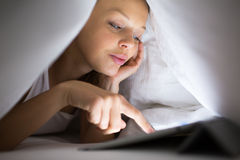 Pretty, young woman using her tablet computer in bed Royalty Free Stock Photography