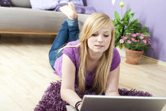 Pretty young woman using laptop. At home stock images