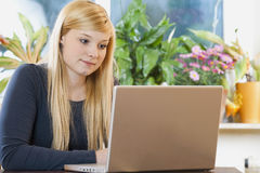 Pretty young woman using laptop. At home royalty free stock images