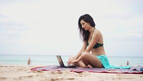 Pretty young woman using laptop on beautiful tropical beach. Girl working while being on vacation in paradise. Concept