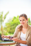 Pretty, young woman using a laptop computer at home Royalty Free Stock Image