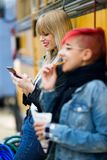 Pretty young woman using the mobile phone while her friend eating potatoes in the street. Royalty Free Stock Photography