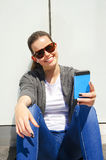 Pretty young woman using mobile phone over white wall Royalty Free Stock Image